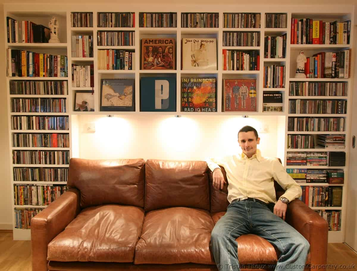 Tristan Titeux sitting on sofa with random bespoke shelving unit around him