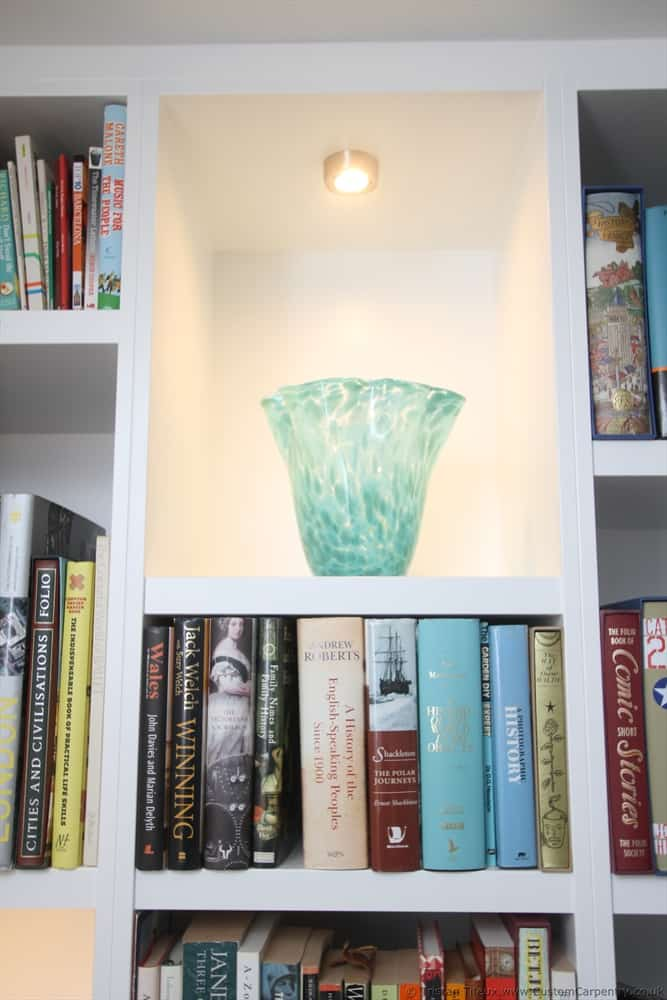 A vase inside a white bespoke shelving unit