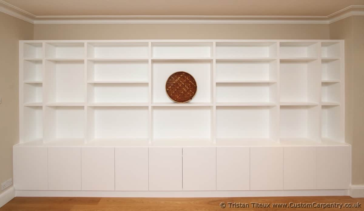 Bespoke shelving hand painted white, with random compartments, and deeper cupboard section below