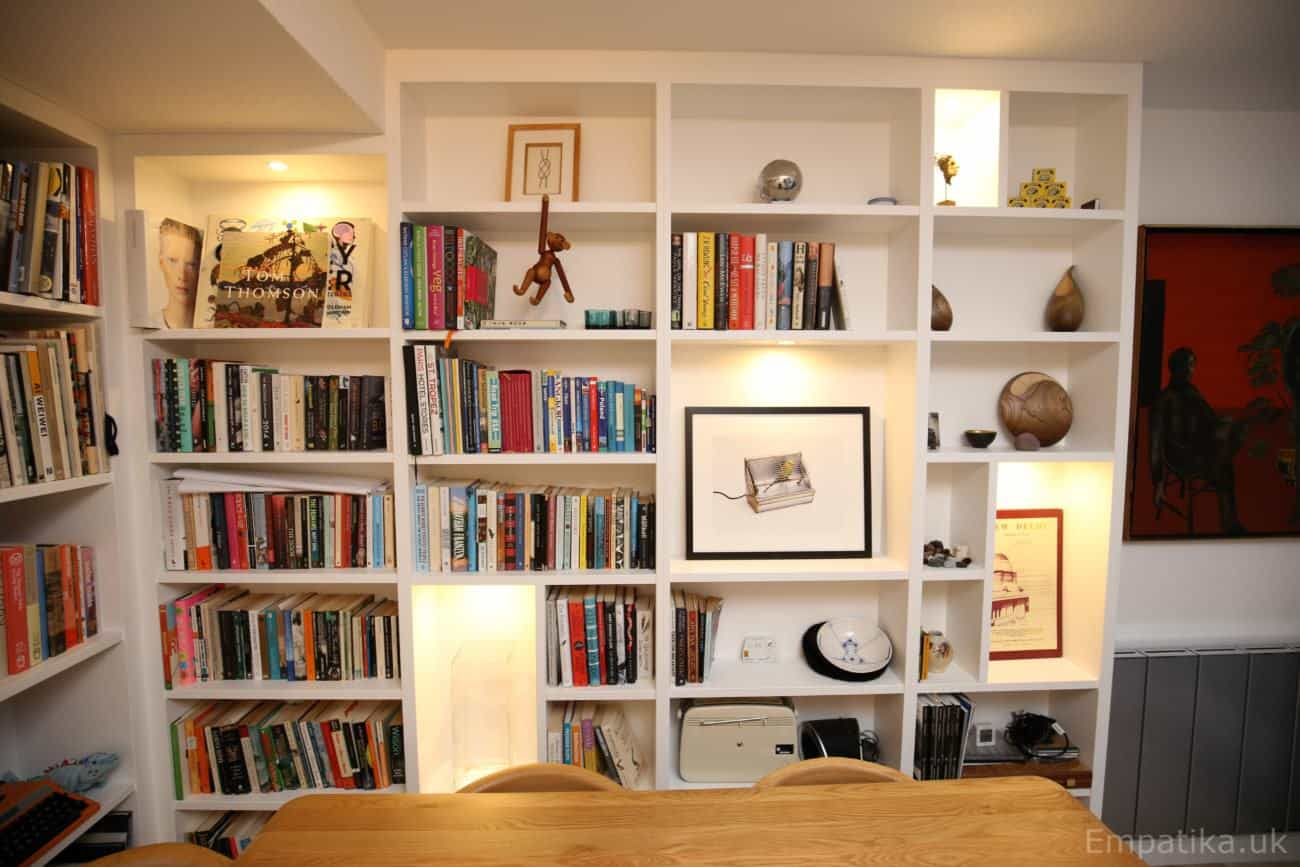 Fitted floor to ceiling display unit library bookcases with accent asymmetrical shelves with LED lights